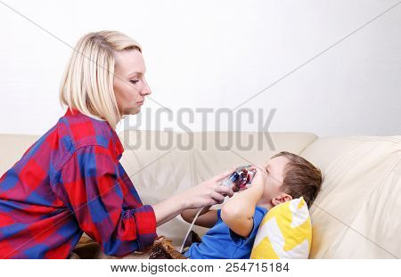 Boy Breathe Through Nebulizer Mother Holds A Nebulizer Mask In The Boy's Face During Inhalation. Sic