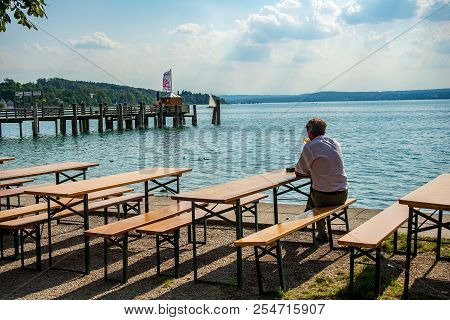 Herrsching,germany-august 20,2018: A Man Sits By Himself In A Biergarten Looking Out To The Waters O