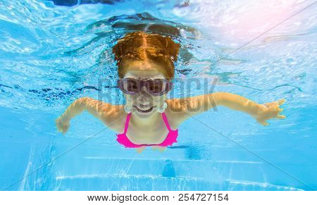 Smiling little girl in swim goggles swimming underwater in pool. Teenage girl diving underwater