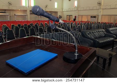 The Microphone Is Located On Podium Stand At The Center Of The Room Is Covered With A Red Carpet Wit