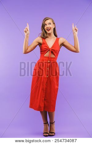 Full length portrait of a pretty young woman in red dress posing while pointing fingers up isolated