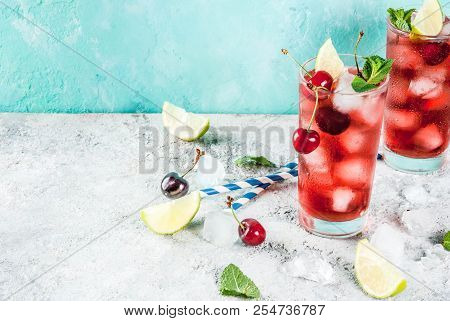 Summer Iced Refreshment Drink, Cherry Cola Lemonade Or Mojito Cocktail In Tall Glass, On Light Blue