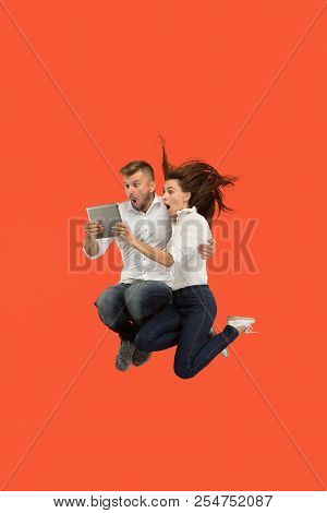 Jump Of Young Couple Over Red Studio Background Using Laptop Or Tablet Gadget While Jumping. Runnin