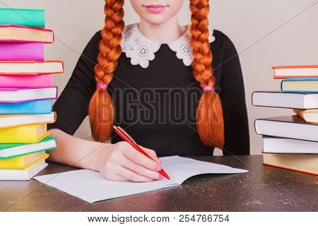 Redhead School Girl In School Uniform Sits At Desk On Gray Background. Colored Text Books On Table.