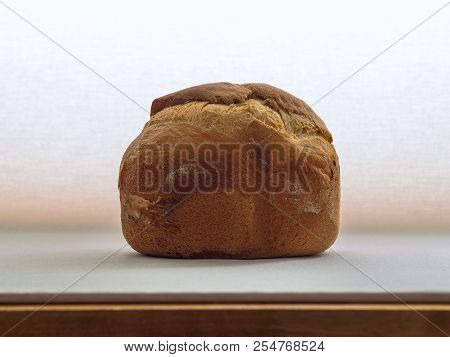 Loaf Of Fresh Crusty Bread Cooked In Bread Machine On Bright Background