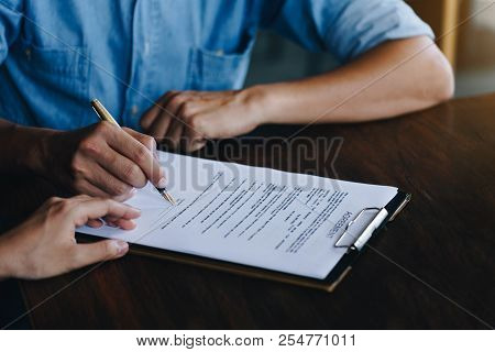 Close Up Of Customer Signing A Paper Document For Buying House. Estate Agent Pointing Finger Showing