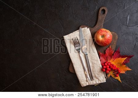 Autumn Composition With Copy Space Of Kitchen Utensils. Cutting Board, Knife And Fork On Dark Backgr