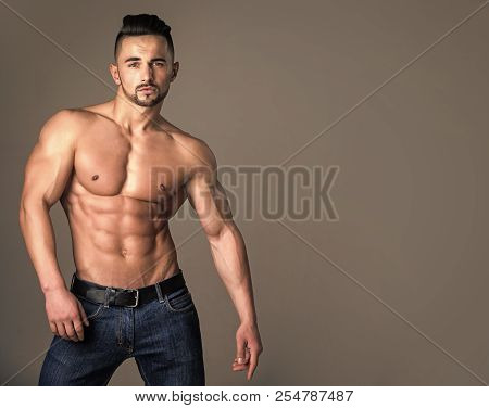 Dieting And Fitness. Coach Sportsman With Bare Chest In Jeans. Athletic Bodybuilder Man On Grey Back
