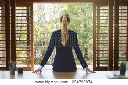 Female Business Woman Is Looking Out The Garden Windows For Success