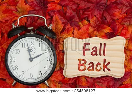 Daylight Savings Time Message, Some Fall Leaves And Retro Alarm Clock With Text Fall Back On Wood Fr