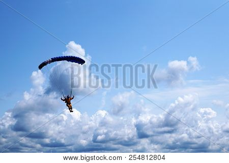 Skydiver Under A Dark Blue Little Canopy Of A Parachute On The Background A Blue Sky And Clouds, Clo