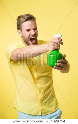 Macho hold plastic spray bottle as gun yellow background. Guy with water spray in hand pretend shooting attack. Housework and sanitary concept. Take care about moisturizing. Moisturizing concept. poster