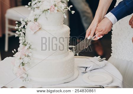 Bride And Groom Holding Knife And Cutting Stylish White Wedding Cake With Flowers. Modern Big Weddin