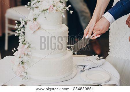 Bride And Groom Holding Knife And Cutting Stylish White Wedding Cake With Flowers. Modern Big Weddin