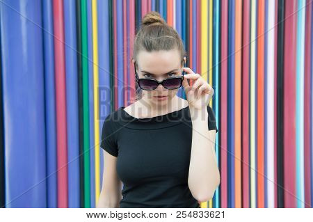 Fashion Urban Style Concept. Lady Mysterious Face Picking Out Of Black Eyeglasses In Front Of Stripe