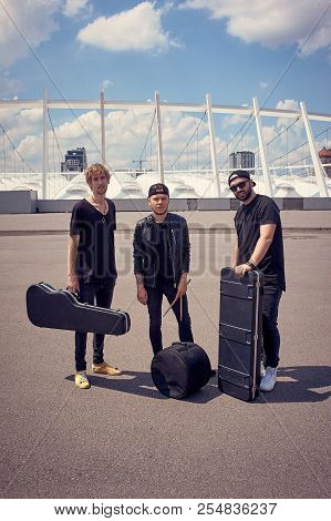 Rock Music Band With Musical Instruments In Cases Standing On Street