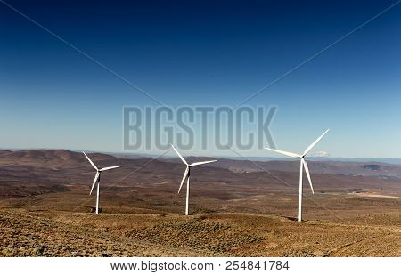 Green Sustainable Energy Windmill Power Turbine Electricity Generators On Rolling Hills With Clouds