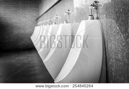 White Urinals In Men Public Toilet. Urinals Made Of Ceramic In A Row In Gentleman Restroom. Take A P