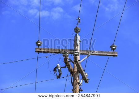 Wires And Telephone Pole. Conceptual Image Of Telephone Pole And Wires Against A Blue Sky.