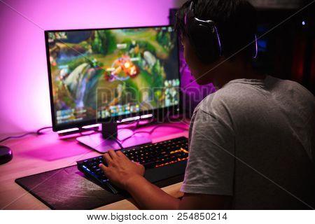 Photo of teenage gamer boy playing video games on computer in dark room wearing headphones and using backlit colorful keyboard