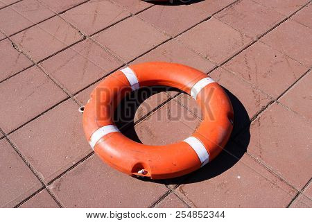 A Large Round Orange Plastic Life Ring For Safety And Rescue People In The Water Lies On The Stone F