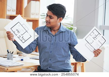 Cheerful young engineer showing two variants of apartment plan poster