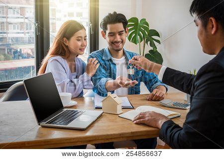 Sale Representative Offer The House Key Chain To Asian Young Couple After Signed Contact House Purch
