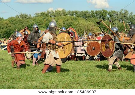 """MOSCOW - SEPTEMBER 4: Two unidentified warriors compete in the middle of a big battle reconstruction at the international festival of fights """"Times and Epoch"""" on September 4, 2011 in Moscow, Russia. The event's attendance is about 130,000 people."""