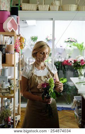Woman Florist Making Bouquet Of Pink Flowers Indoor. Female Florist Preparing Bouquet Of Roses In Fl