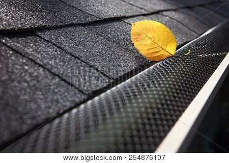 Plastic guard over gutter on a roof with a leaf stuck on the outside