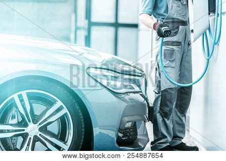 Plug In Hybrid Vehicle And The Charging Station. Worker Preparing To Hookup Modern Vehicle To The Po