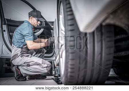 Used Car Under Maintenance. Caucasian Car Mechanic Looking For Potential Problems Inside The Vehicle