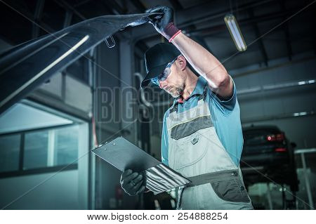 Vehicle Engine Problem. Caucasian Technician In His 30s Inside Dealership Service Area Taking Detail