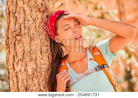 Dehydrated tired hiking woman thirsty feeling exhausted of heat stroke. Girl with headache from hot temperature on outdoor activity hiker lifestyle. poster