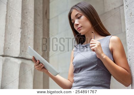 Tablet business woman worker serious working at office or courthouse reading news email. Asian Businesswoman lawyer using pc computer with reading glasses. Multiracial Caucasian Chinese professional.