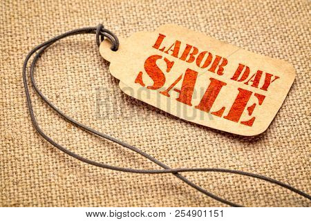 Labor Day sale sign - a paper price tag with a twine against burlap canvas