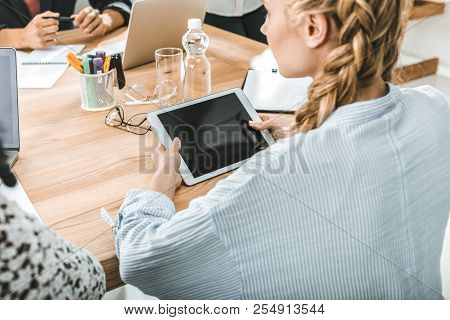 Side View Of Businesswoman Holding Digital Tablet While Sitting At Table During Meeting With Colleag
