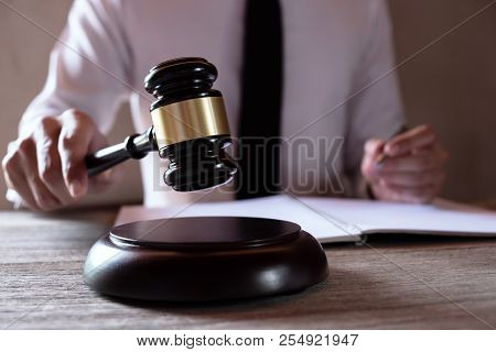 Male lawyer working with lawsuit papers on tabel in courtroom. justice process and law, attorney, co