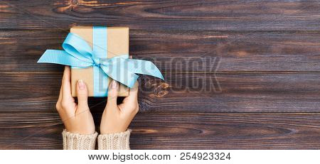 Woman Hands Give Wrapped Valentine Or Other Holiday Handmade Present In Paper With Blue Ribbon. Pres