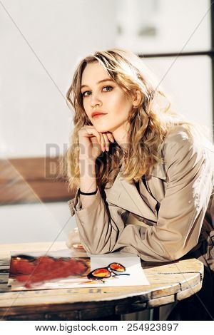 Beautiful young woman spends time in a caf?.  Beauty, city fashion.