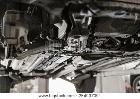 Car Mechanic Inspecting Car Wheel And Repair Suspension Detail. Lifted Automobile At Repair Service