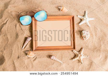 Wooden Frame, Sunglasses And Seashells On Sand Beach