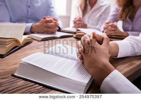Woman's Praying Hand On Bible