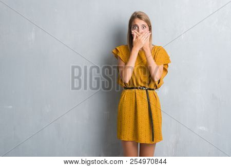 Beautiful young woman standing over grunge grey wall wearing a dress shocked covering mouth with hands for mistake. Secret concept.