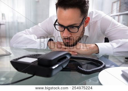 Young Businessman Waiting For A Call On Landline