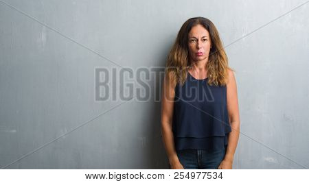 Middle age hispanic woman standing over grey grunge wall depressed and worry for distress, crying angry and afraid. Sad expression.
