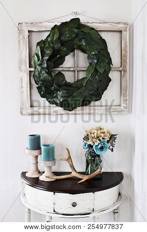 Old Farmhouse Window Decorated With A Homemade Magnolia Leaf Wreath Hung On An Interior Wall Over Ru