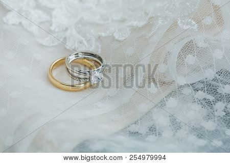 Bride Diamond Rings   And Groom Gold Wedding Band On Delicate Lace Wedding Dress Detail Close Up Jus