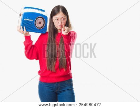 Young Chinese woman over isolated background holding vintage radio pointing with finger to the camera and to you, hand sign, positive and confident gesture from the front