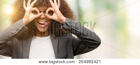 African american business woman wearing glasses doing ok gesture like binoculars sticking tongue out, eyes looking through fingers. Crazy expression.